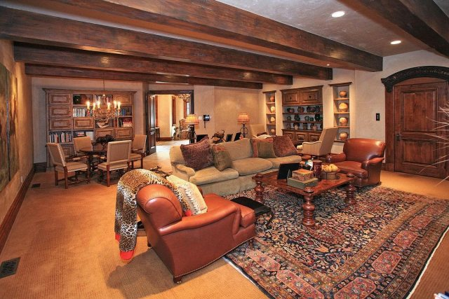 Another living area has a beautiful oriental rug and wooden beams overhead.