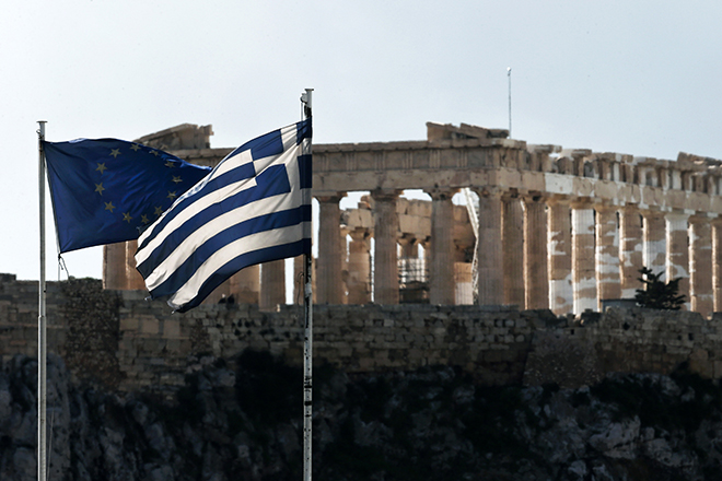 An EU and a Greek national flag flutter in front of the Parthenon temple in Athens